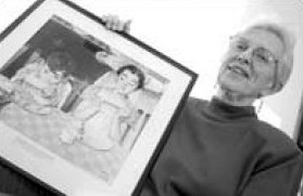 Mary Jane Butler Gmelin Gill poses in 2001 with a portrait of herself at age 7, painted by her neighbor, Norman Rockwell.
